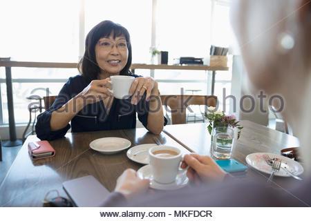 Les femmes âgées actives les amis de boire du café et de parler au café Banque D'Images