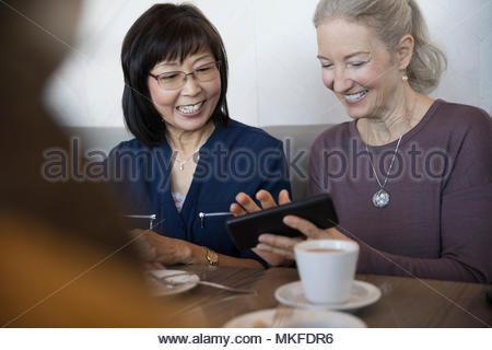 Smiling senior women using smart phone in cafe Banque D'Images
