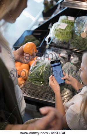 Mère et fille avec smart phone liste des épiceries et des légumes au cours du marché Banque D'Images