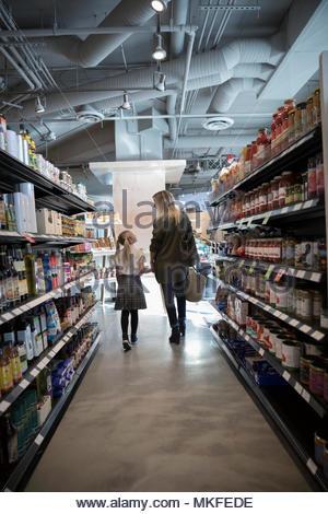Tendre mère et fille se tenant la main, les emplettes dans l'allée du marché Banque D'Images