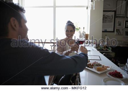Jeune couple toasting date de verres à vin en bar Banque D'Images