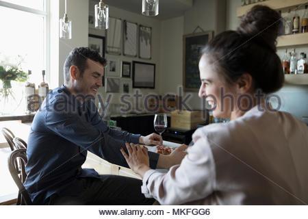 Jeune couple sur la date, rire et boire du vin rouge en bar Banque D'Images