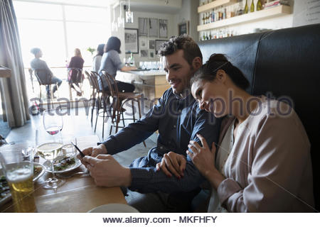 Young couple with smart phone at table bar Banque D'Images