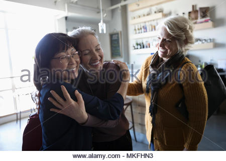 Happy senior women friends accueil, hugging in cafe Banque D'Images