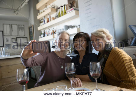 Heureux, confiant senior women friends en tenant avec selfies smart phone in cafe Banque D'Images