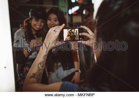 Jeune femme avec millénaire téléphone appareil photo photographier friends in nightclub Banque D'Images