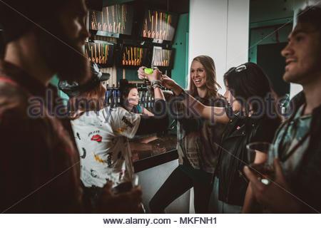Amis millénaire prenant des coups, faire la fête en discothèque bar Banque D'Images