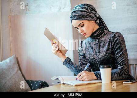 Les jeunes femmes musulmanes d'Asie travailler avec tablet et boire un café dans un café Banque D'Images