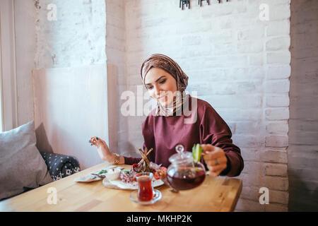 Young Asian Muslim woman pouring tea sur la coupe. Banque D'Images