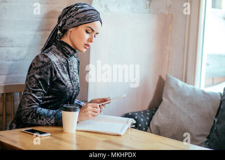 Arabian Woman working in coffee shop with digital tablet et boivent du café Banque D'Images