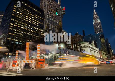 NEW YORK - Etats-Unis - 31 octobre 2017 - Une longue exposition photo de voitures traversant une intersection à New York pendant que la vapeur qui sort du trou.