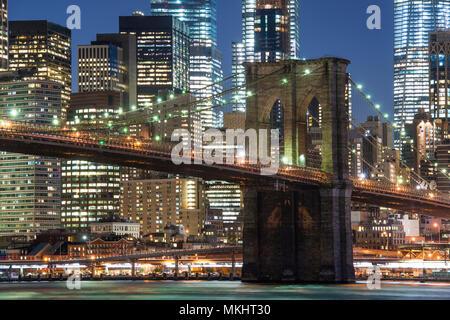 Le Pont de Brooklyn et de Manhattan Skyline illuminée le soir avec ciel bleu et lisse la surface de l'eau coup de côté de Brooklyn, New York, USA. Banque D'Images