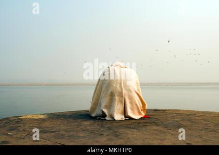 Un saint homme vêtu de blanc est en priant et en méditant sur l'un des nombreux Ghats de Varanasi en face de la rivière sacrée, le Gange en Inde. Banque D'Images