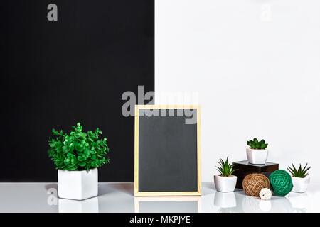 Cadre en bois noir avec place pour le texte. Des maquettes. Cette chambre élégante dispose d''intérieur. Plante verte dans un pot blanc sur noir-blanc wall background Banque D'Images