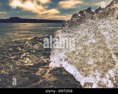 La fonte des glaces sur la plage de sable. Détail de banquise avec fissures profondes à l'intérieur. La fin de l'hiver crue venue. Banque D'Images