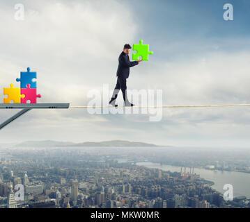 Businessman porte un morceau de casse-tête pendant qu'il marche sur une corde. concept de pièce manquante