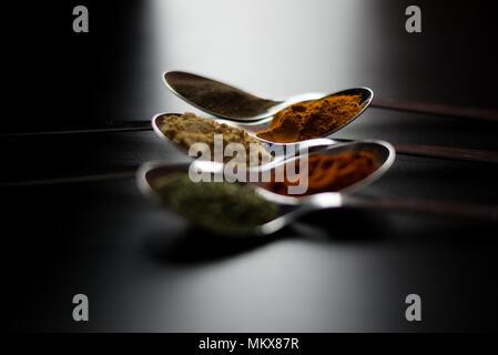 Épices colorés en cuillères d'argent, posé sur une table en bois noir. Poivre, sel, poivre, basilic, moutarde Banque D'Images