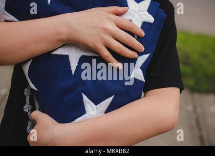 Un jeune garçon tenant un drapeau américain pliée.