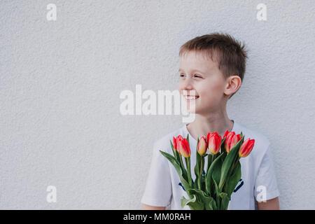 Jeune garçon tenant un bouquet de tulipes rouges et souriant de côté. Donner un bouquet comme un cadeau. Mur Blanc, l'arrière-plan de l'espace de copie. Banque D'Images