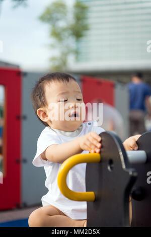 Peu de tout-petit garçon asiatique s'amuser sur l'aire de jeux Banque D'Images