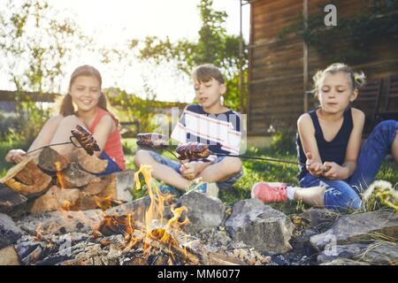 Les enfants bénéficient de camp. Frères et sœurs (famille) faire griller les saucisses sur le jardin au coucher du soleil. Banque D'Images
