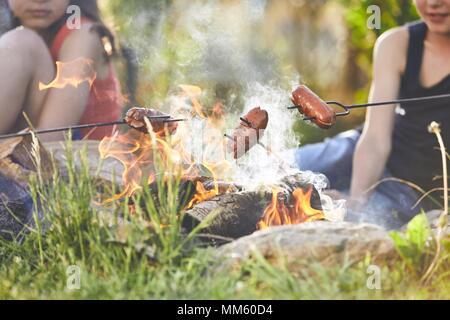 Les enfants bénéficient de camp. Les filles (famille) faire griller les saucisses sur le jardin. Banque D'Images