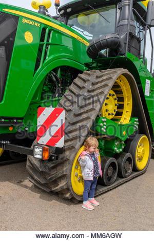 Célébrons 100 ans de John Deere. John Deere 9620RX à chenilles, avec un jeune enfant debout à côté de l'avant crawler pour donner une idée d'échelle. Banque D'Images