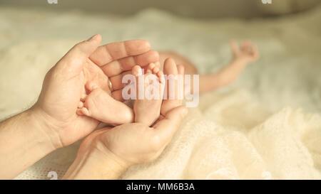 .Happy mother hugging les jambes d'un bébé nouveau-né. Banque D'Images