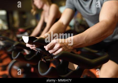 Gros plan des mains d'un homme autour de la salle de sport, l'exercice de jambes faisant cardio vélo vélos. Dans un couple de spinning portant des vêtements de sport. Banque D'Images