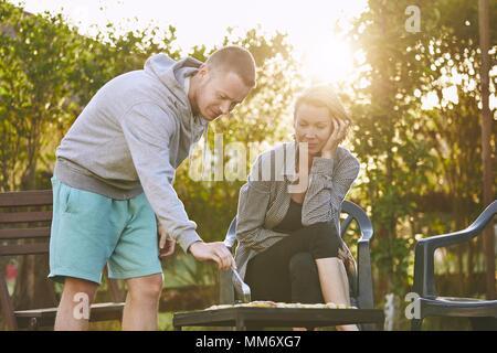 L'été sur le jardin. Jeune couple barbecuing contre chalet au coucher du soleil. Banque D'Images