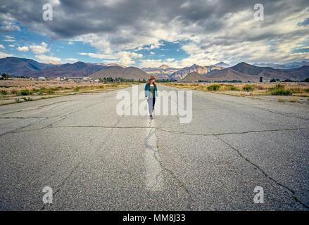 Femme au chapeau et chemise à carreaux la marche sur la grande route asphaltée avec montagnes et fond de ciel nuageux Banque D'Images