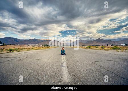 Femme au chapeau et chemise à carreaux assis avec la jambe croisée sur la large route asphaltée avec montagnes et fond de ciel nuageux Banque D'Images