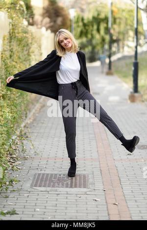 Funny blonde woman smiling en contexte urbain. Jeune fille vêtu de noir veste blazer et pantalon à rayures debout dans la rue. Jolie femelle avec Banque D'Images