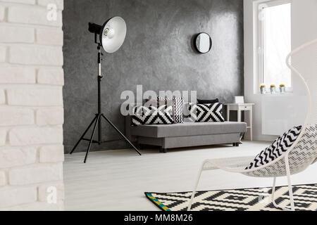 Grand salon blanc et gris conçu avec créativité. Grande lampe moderne à côté du canapé gris dans cette chambre spacieuse Banque D'Images