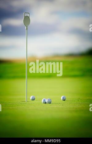 Collecter les balles de golf autour d'un axe sur un practice putting green. Banque D'Images