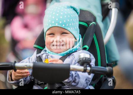 Cute baby girl dans sa circonscription de chaleur en tricycle spring park Banque D'Images