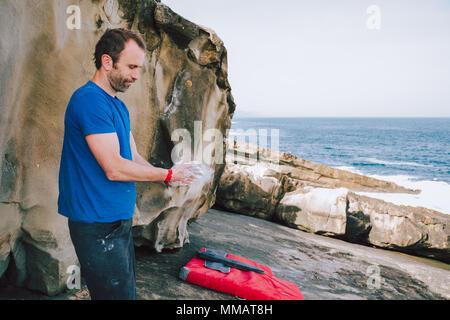 Jeune homme grimpeur dans ses mains de revêtement en poudre de magnésium de craie pour l'escalade dans la côte Banque D'Images