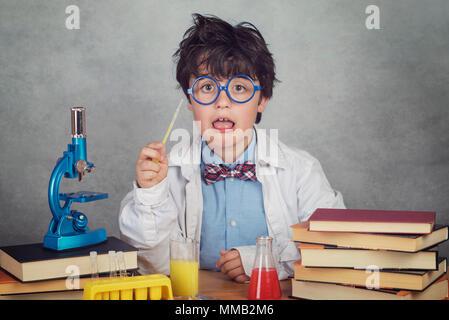Garçon fait des expériences scientifiques dans un laboratoire sur fond gris Banque D'Images