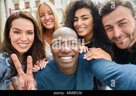 Groupe multiracial d'amis prenant en selfies une rue urbaine avec un homme noir en premier plan. Trois jeunes femmes et deux hommes portant des vêtements décontractés. Banque D'Images