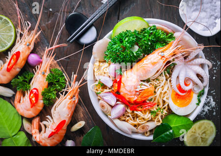 Fruits de mer chaude et nouilles en bol blanc sur la table en bois Banque D'Images