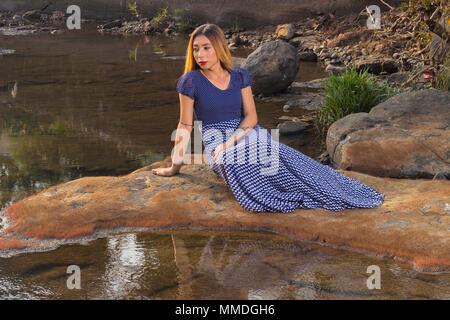 Pose d'un côté long femme avec robe bleue assise sur un rocher à l'eau à Banque D'Images