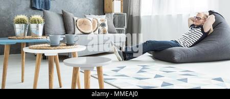 Vue panoramique d'un jeune homme se détendre dans un sac de séance dans un studio moderne Banque D'Images