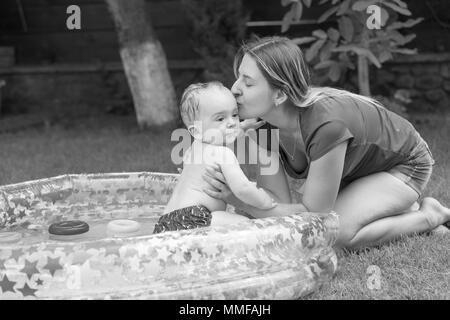 Photo en noir et blanc de jeune mère embrassant son bébé dans une piscine gonflable Banque D'Images