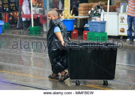Un jeune garçon grassouillet portant un sac à déchets pour le protéger de la pluie travaille sur les détails et tire un bac pour les ordures ménagères. Banque D'Images