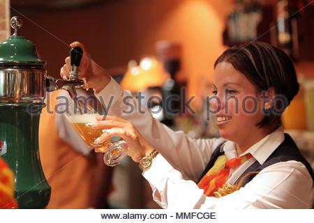 Un barman cubain se verse une bière cubaine typique dans un bar cubain à un resort hotel. Banque D'Images