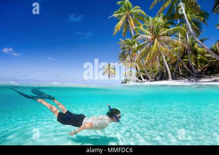 L'homme nage en eaux tropicales claire en face de l'île exotique Banque D'Images