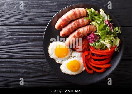 Saucisses frites maison enrobé de bacon, d'œufs, de la sauce et salade fraîche gros plan sur une plaque horizontale. haut Vue de dessus Banque D'Images