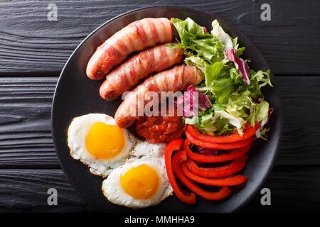 Les porcs en petit-déjeuner saucisses frites couvertures enrobé de bacon, d'œufs, de la sauce et salade fraîche gros plan sur une plaque horizontale. haut Vue de dessus Banque D'Images