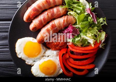 Saucisses frites enrobé de bacon, oeufs et salade fraîche gros plan sur une plaque horizontale. haut Vue de dessus Banque D'Images