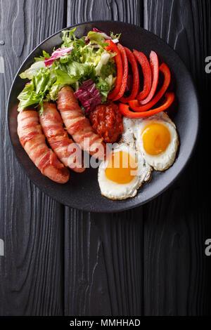 Saucisses frites maison enrobé de bacon, d'œufs, de la sauce et salade fraîche gros plan sur une assiette. Haut Vertical Vue de dessus Banque D'Images